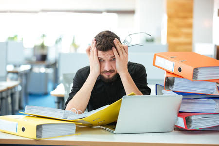 tired businessman: Tired businessman working with papers in office Stock Photo