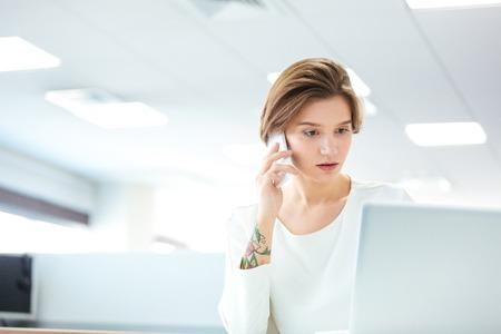 mujer pensativa: mujer joven y bonita pensativo que trabaja con el ordenador port�til y hablando por tel�fono celular en la oficina