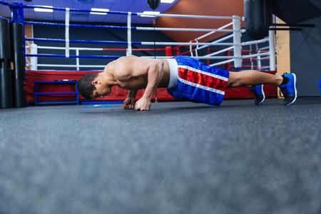 push ups: Boxer doing push ups near boxing ring