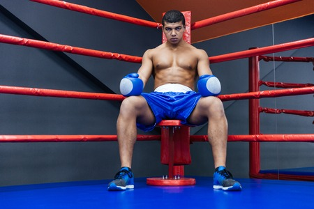 Professional male boxer sitting in the corner of the boxing ring
