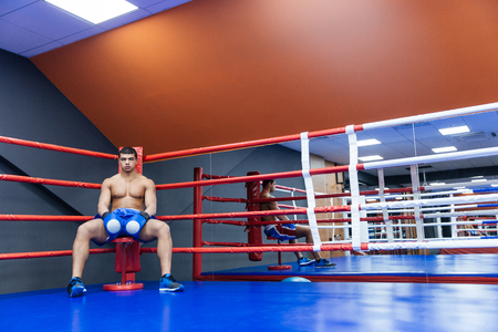 looking in corner: Male boxer sitting in the corner of the boxing ring and looking at camera