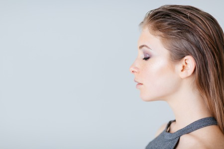 closeup view: Side view portrait of a lovely woman over gray background