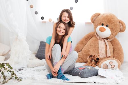 Dos hermosas hermanas sonriente sentado juntos en la habitación de los niños Foto de archivo