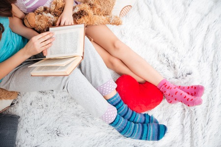 striped pajamas: Closeup of beautiful legs of two young women sitting and reading a book on soft carpet Stock Photo