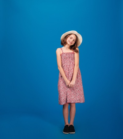 sundress: Full length of pretty cheerful little girl in sundress and hat standing and looking at camera over blue background