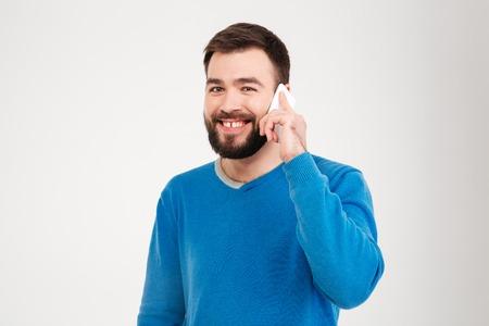uomini belli: Uomo sorridente parlando al telefono isolato su uno sfondo bianco