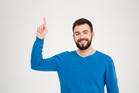 25 29: Smiling casual man pointing finger up isolated on a white background Stock Photo