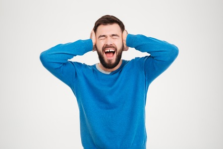 outcry: Young man covering his ears and screaming isolated on a white background