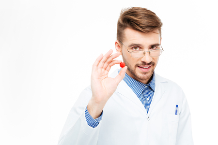 hormone  male: Handsome male dotor holding red pill isolated on a white background Stock Photo
