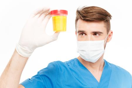 cirujano: Cirujano de sexo masculino con la botella máscara de celebración de la muestra de orina aislada en el fondo blanco Foto de archivo