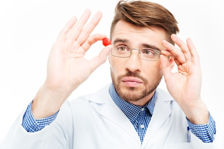 hormone  male: Young male doctor in glasses looking on pill isolated on a white background