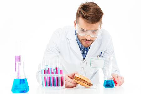Male chemist making GMOs food isolated on a white background Reklamní fotografie