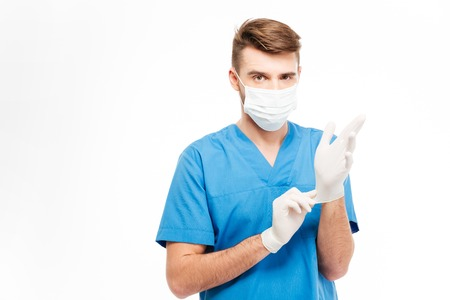 sterility: Male doctor putting on gloves isolated on a white background