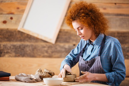 earthen: Creative young woman potter with curly red hair making earthen dishes in workshop