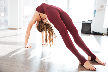 woman barefoot: Attractive young woman bending and stretching on the floor in yoga studio