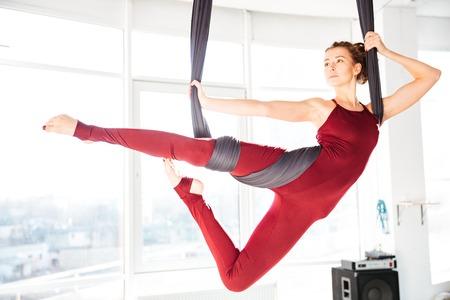 Ernstige aantrekkelijke jonge vrouw doet anti-zwaartekracht yoga met behulp van hangmat in studio