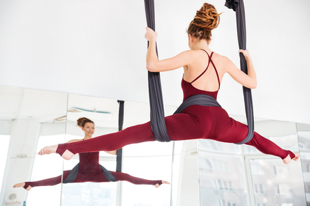 Back view of smiling pretty young woman doing twine using hammock on antigravity youga class Imagens - 53499589