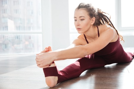 girl in sportswear: Focused young woman with dreadlocks sitting and stretching legs in front of the window