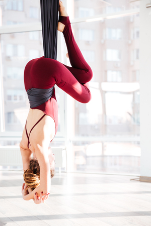 Back view of young woman practicing antigravity yoga exercises in studio