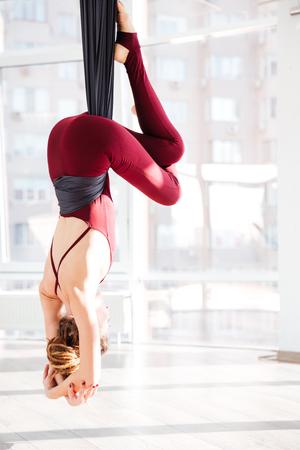Vista trasera de la joven la práctica de ejercicios de yoga antigravedad en estudio Foto de archivo