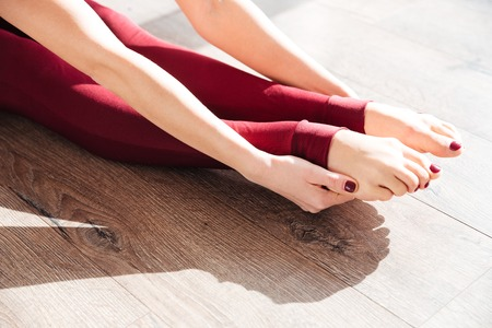 woman barefoot: Closeup of slim legs of young woman gymnast sitting and stretching on wooden floor