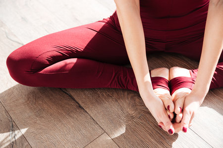 woman barefoot: Closeup of hands and legs of young woman doing yoga barefoot