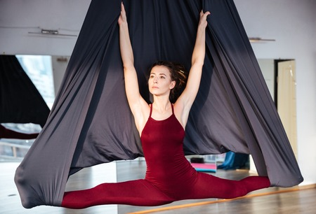 hammock: Beautiul inspired young woman doing aerial yoga on black hammock in studio Stock Photo