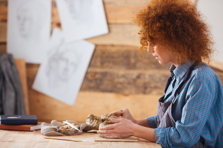 woman profile: Profile of focused redhead young woman ceramist creating sculpture using clay in pottery workshop