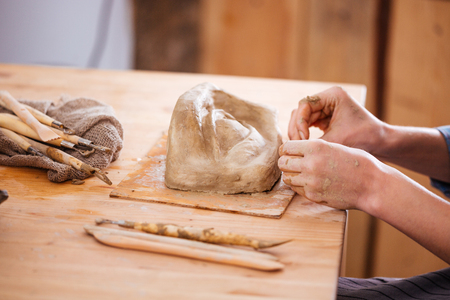 sculpture: Closeup of hands of young woman ceramist working and finishing sculpture with clay on wooden table in workshop