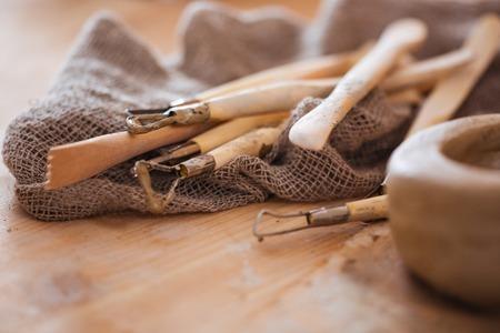 Conjunto de herramientas de arte y artesanía de escultura sucios en la mesa de madera en el taller de cerámica Foto de archivo