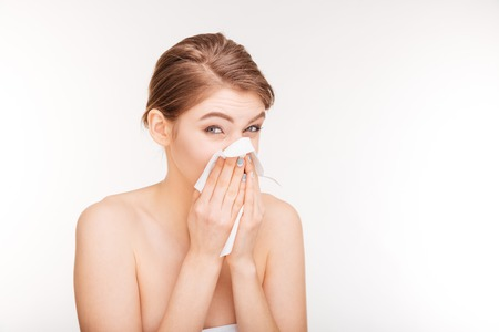 rheum: Beauty portrait of unhappy young woman catched a cold and using paper handkerchief over white background