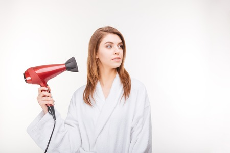 thoughful: Beautiful thoughful young woman in bathrobe drying her hair with dryer over white background