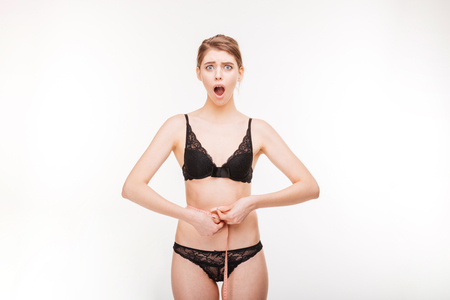shoked: Shoked beautiful young woman in lace lingerie measuring her waist over white background