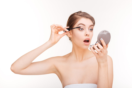 fashion girl: Charming woman applying mascara on her eyelashes isolated on a white background Stock Photo