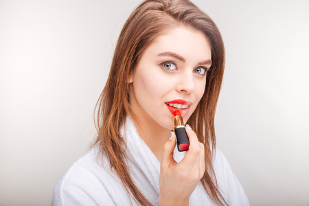 red bathrobe: Attractive lovely young woman in bathrobe testing red lipstick on her lips over white background Stock Photo