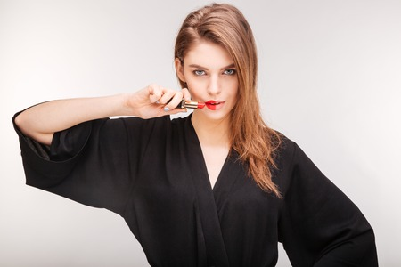 red bathrobe: Gorgeous attractive young woman in black bathrobe demonstrating red lipstick on half of her lips over white background