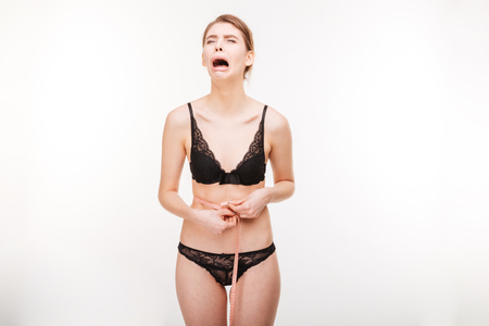despairing: Despairing crying young woman in black lingerie standing and measuring her waist over white background