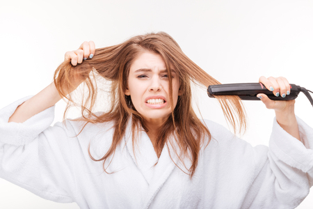 Angry irritated young woman straightening her hair using hair straightener over white background Stok Fotoğraf