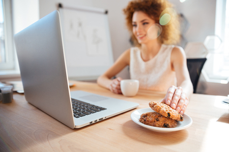 Smiling pretty redhead young business woman drinking coffee with cookies on workplace and using laptop Stock Photo