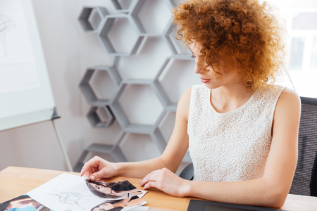 fashion photos: Pretty curly redhead young woman fashion designer sitting and choosing models on photos in office