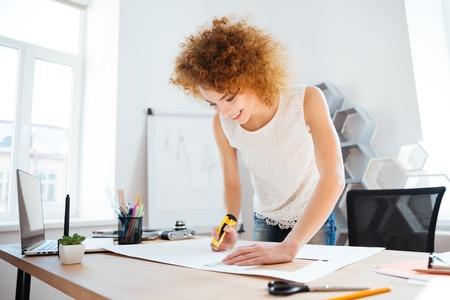 papeleria: Redhead sonriente mujer joven fotógrafo con un cuchillo y la hoja strationery cuttung de papel en la oficina