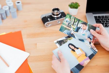 Bovenaanzicht van foto's van modellen holded door jonge vrouw fotograaf aan de tafel