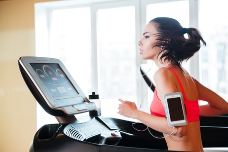 Attractive concentrated young woman running on treadmill in gym and listening to music from blank screen mobile phone