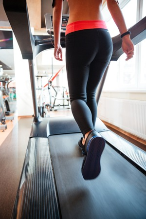 Back view of attractive young sportswoman in black leggings running on treadmill in gym