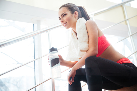 Happy beautiful young sportswoman resting and drinking water on stairs in gym Stockfoto