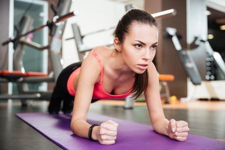 Starke schöne junge Sportlerin, die Plankenübung auf Matte in der Turnhalle tut Standard-Bild - 53519066