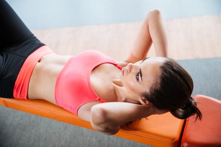 laying abs exercise: Focused pretty young sportswoman doing abs crunches on bench in gym
