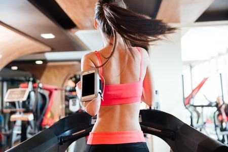 personas de espalda: Vista trasera de la joven y bonita mujer deportista con el teléfono inteligente de pantalla balnk corriendo en la cinta en el gimnasio