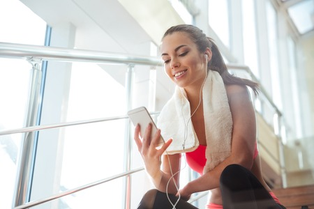 Vrolijke mooie jonge vrouw, zittend op de trap in de gymzaal en het luisteren naar muziek