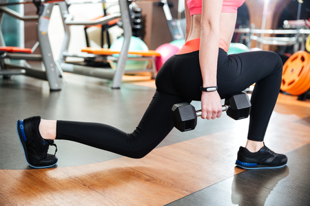 Attractive young woman athlete doing squats with dumbbells in gym Stock Photo